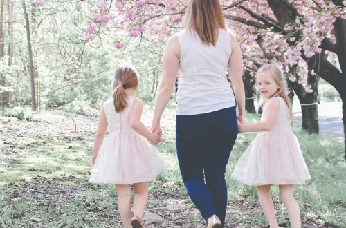 mom walking with two daughters by cherry blossom trees